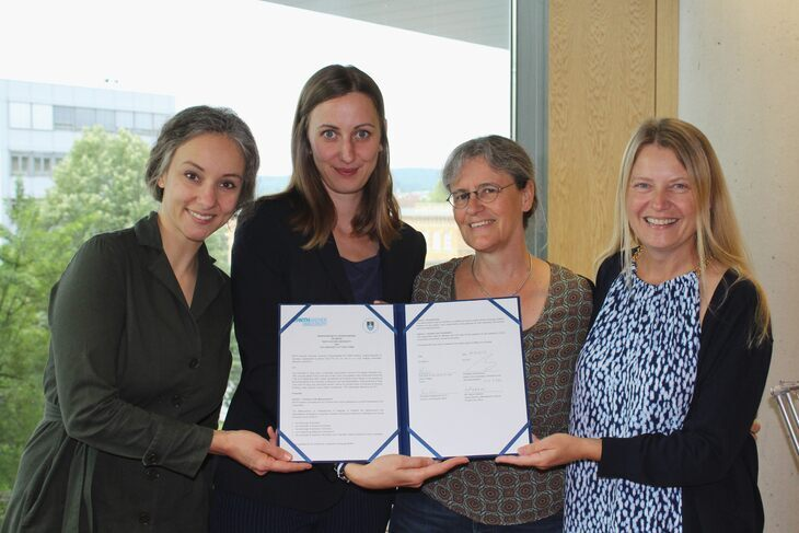 Four women presening an official document